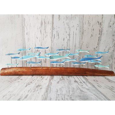 Large blue school of fish on driftwood